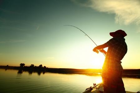 pescador: Joven de pesca en un lago en el barco al atardecer Foto de archivo