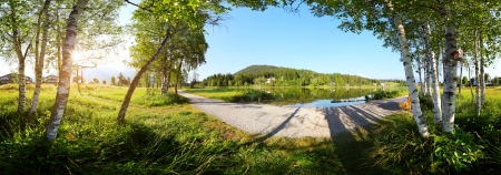 Panorama of a morning pond and gravel walkway. Seefeld, Austria
