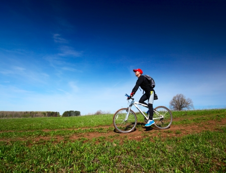 space weather tire: Young man cycling on a rural spring road at sunny day Stock Photo