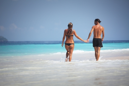 actueel: Young couple walking on the topical beach