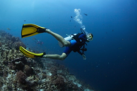 Scuba diver finning underwater and exploring dive spot photo