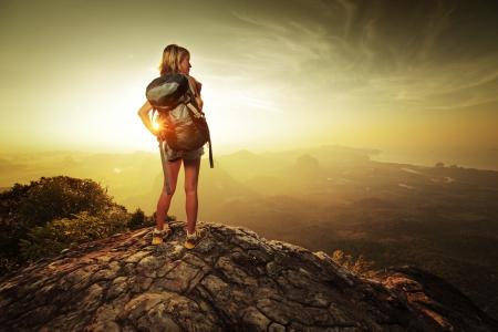女性ハイカーのバックパックを山の上に立っていると、日の出を楽しんで