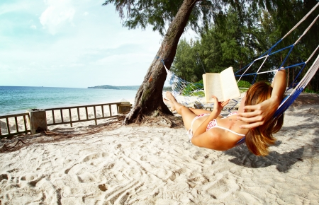 Young woman relaxing with a book in hammock on tropical beach photo