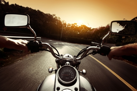 blurr: Driver riding motorcycle on an asphalt road through forest