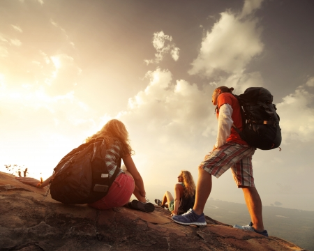 tourist destination: Group of hikers relaxing on top of a mountain and enjoying sunrise