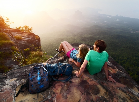 Young hikers relaxing on top of a mountain and enjoying sunrise Stock Photo