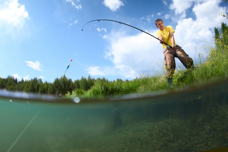 Young man fishing on a green ponds coast with underwater view of weed on a bottom