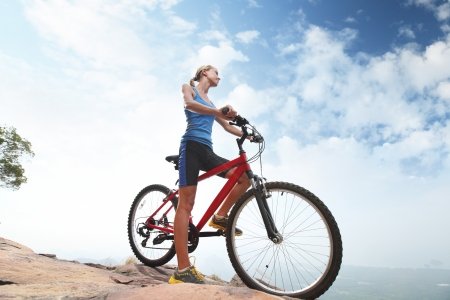 woman hiking: Young sporty lady standing with bicycle on a blue sky background