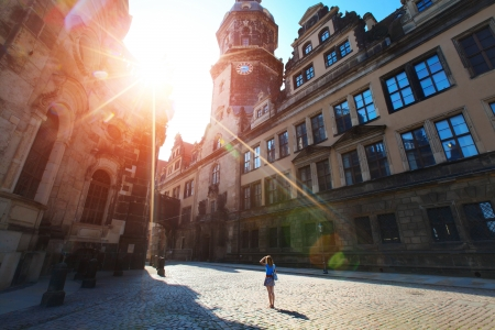 Young lady tourist standing in front of old building in Dresden in a sunny day Stock Photo