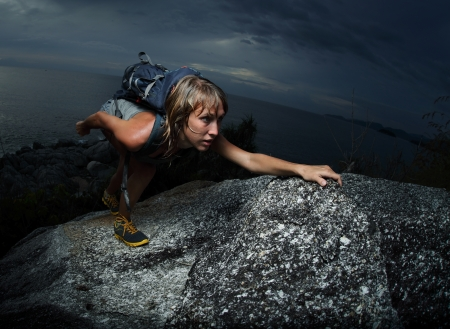 Hiker with backpack climbing natural rocky wall on a dark cloudy background. There are water drops on the skin