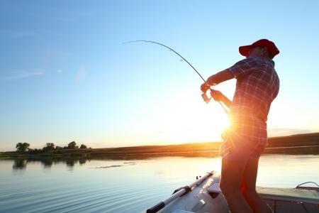 hombre pescando: Joven de pesca en un lago en el barco al atardecer Foto de archivo