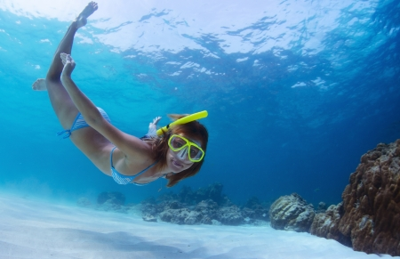 Young lady snorkeling and diving on a breath hold in a clear tropical sea Stock Photo