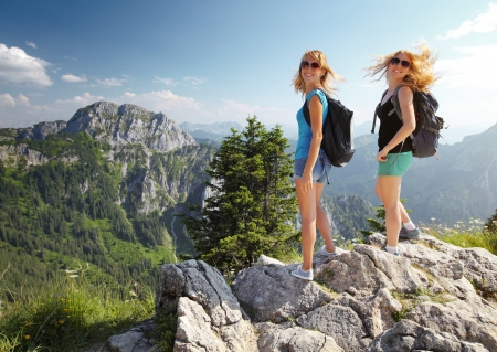 two on top: Two smiling ladies with backpacks standing on top of a mountain and looking to a camera Stock Photo
