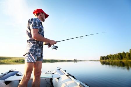 hombre pescando: Joven de pesca en un lago de la embarcaci�n Foto de archivo