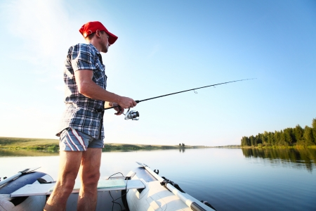 pike: Young man fishing on a lake from the boat