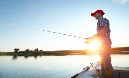 lure: Young man fishing on a lake from the boat at sunset