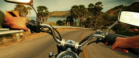 Driver riding motorcycle on an asphalt road in a tropics photo