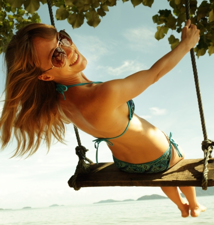 swinging: Young happy woman having fun on a swing on a tropical beach