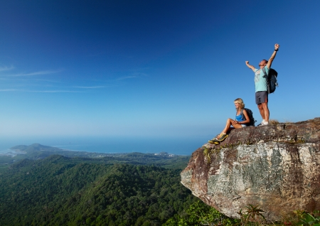 Young active couple enjoying view from top of a mountain Stock Photo