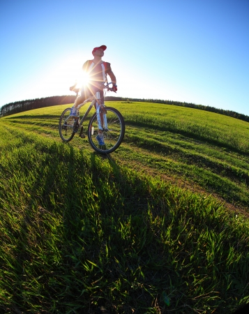 eye traveller: Young man standing with bicycle in a summer meadow at sunset Stock Photo