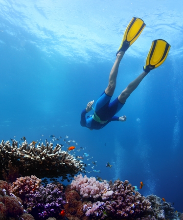 Lady freediver gliding over coral reef in a tropical sea