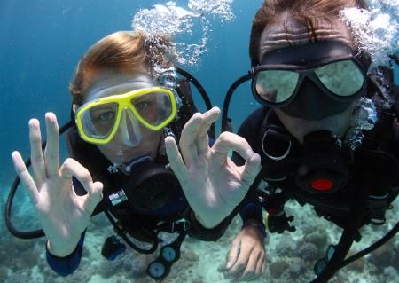 Diepzeeduikers die OK signaal onderwater Stockfoto