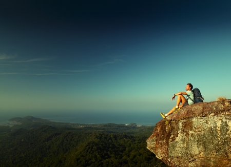 seaview: Male hiker with backpack relaxing on top of a mountain
