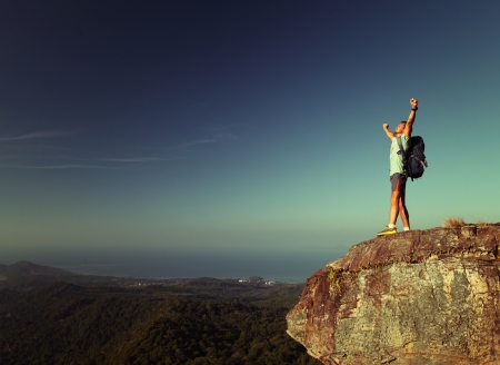 Male hiker with backpack standing on top of a mountain with raised hands photo