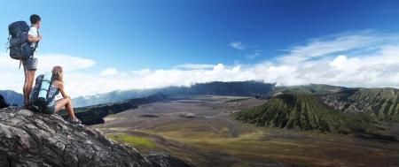 Twee wandelaars met rugzakken ontspannen op de top van een heuvel met uitzicht op de vallei Stockfoto