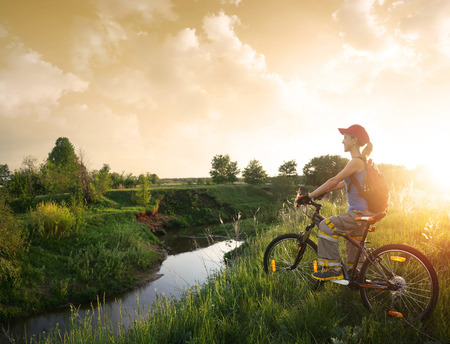 off road biking: Young lady standing with bicycle on a wild meadow by a river at sunset Stock Photo
