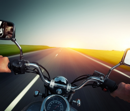 Driver riding motorcycle on an empty asphalt road photo