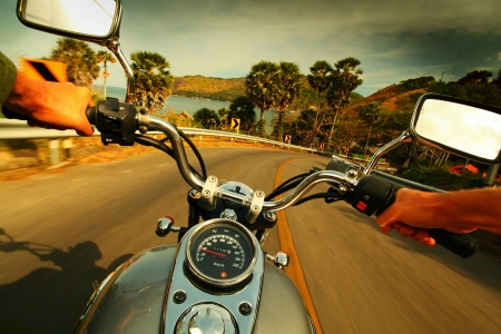 motorcycle: Driver riding motorcycle on an asphalt road in a tropics