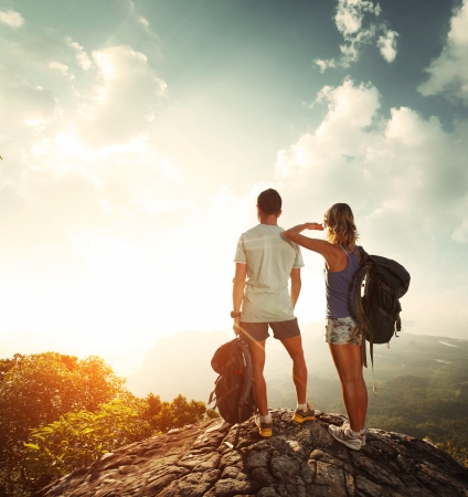 Hikers with backpacks standing on top of a mountain and enjoying valley view