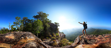 Spherical 360 degrees panorama of a rocky cliff with female hiker standing on an edge with raised hands Stock Photo