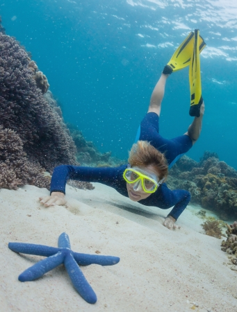 bottom of sea: Young woman swimming over sandy sea bottom and watching the blue sea star Stock Photo