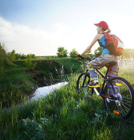 Young lady standing with bicycle on a wild meadow by a river at sunset Stock Photo