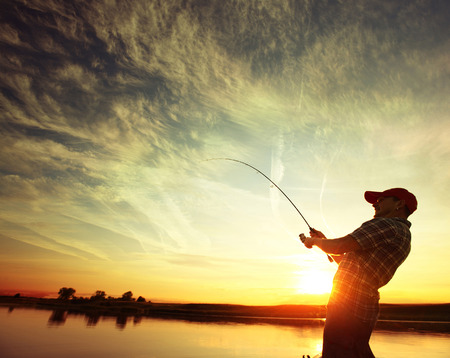 lake shore: Man fishing from a boat at sunset Stock Photo