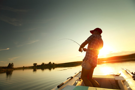 Young man fishing from a boat at sunset photo