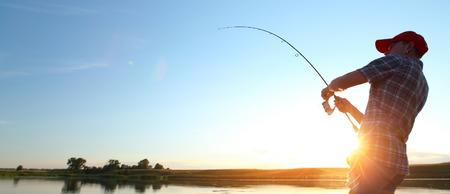 hombre pescando: Pesca del hombre joven al atardecer