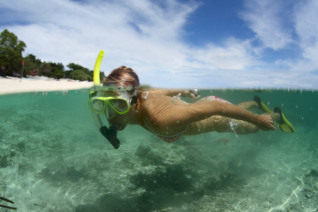 beneath the surface: Young lady snorkeling in a sea