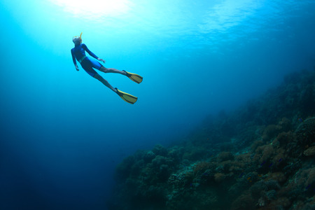 Young woman freediving in a sea over coral reef photo