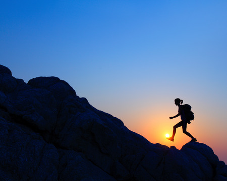 high jump: Hiker with backpack crossing rocky terrain