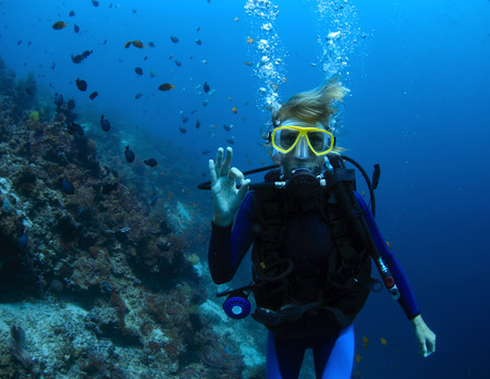 Onderwater schieten van een vrouw die het duiken met scuba door koraalrif en het tonen van ok signaal Stockfoto