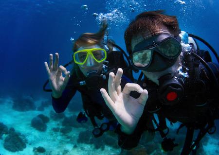 Onderwater schieten van een paar duiken met duiken en die ok signaal. Focus op de hand van een man