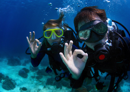 Underwater shoot of a couple diving with scuba and showing ok signal. Focus on a mans hand 版權商用圖片