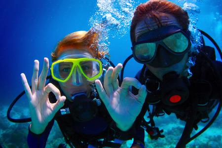 水中撮影のカップルとスキューバ ダイビングと ok 信号を表示
