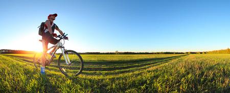 Hombre joven en bicicleta en un camino rural a través del prado verde de la primavera durante el atardecer