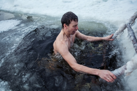Young man swimming in an ice hole in a winter day photo