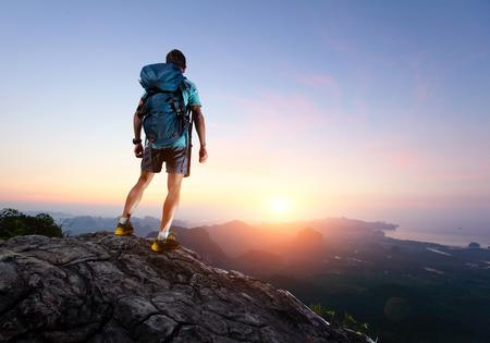 Wandelaar met rugzak staande op de top van een berg en genieten van zonsopgang Stockfoto
