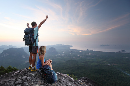 Hikers relaxing on top of a mountain and enjoying sunrise